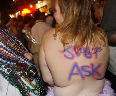 A reveler wanders Boubon Street without her top during the 2008 Mardi Gras celebrations