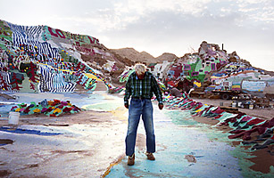"Leonard Knight stands with his art creation ""Salvation Mountain"" in California's Slab City"